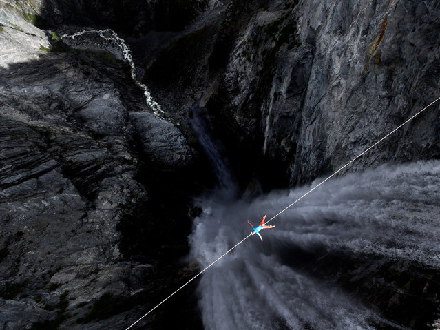 Lukas Irmler lying down on a line across Hunlen Falls. (Photo by Valentin Rapp/Caters News)