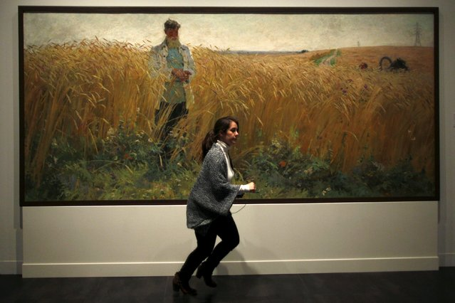 A woman runs next to a painting by Russian-born artist Alexander Bubnov during an international press tour of the Malaga branch of the State Museum of Russian Art of St Petersburg, a day before its inauguration in Malaga, southern Spain March 24, 2015. (Photo by Jon Nazca/Reuters)