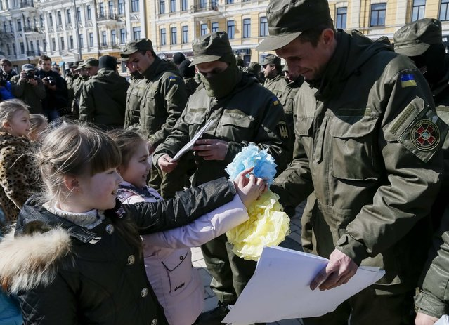 """Children present their paintings to servicemen of the Ukrainian national guard battalion """"Donbass"""" before they depart to the frontlines in eastern Ukraine, in central Kiev, March 17, 2015. (Photo by Gleb Garanich/Reuters)"""