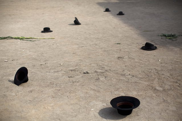 """In this Sunday, March 29, 2015 photo, hats lie scattered after being tossed by dancers during a performance at the Vencedores de Ayacucho dance festival, in the Acho bullring in Lima, Peru. """"The dance is a catharsis, a way for people to express feelings they cannot in other public spaces"""", said Peruvian archaeologist Carmen Cazorla, who studies Andean rituals. (Photo by Rodrigo Abd/AP Photo)"""