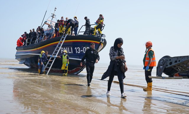 A group of people thought to be migrants crossing from France come ashore from the local lifeboat at Dungeness in Kent, United Kingdom on Tuesday, July 20, 2021, after being picked-up following a small boat incident in the Channel. (Photo by Gareth Fuller/PA Images via Getty Images)