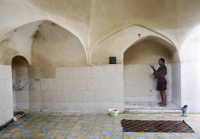 In this November 21, 2014 photo, Heidar Javadi, 39, a bathhouse worker, says prayers during a break, at the Setareh public bathhouse, in Yazd, Iran. (Photo by Ebrahim Noroozi/AP Photo)