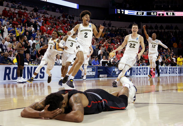 Jordan Poole #2 and teammates of the Michigan Wolverines celebrate Poole's 3-point buzzer beater for a 64-63 win as Devin Davis #15 of the Houston Cougars is seen on the ground during the second round of the 2018 NCAA Men's Basketball Tournament at INTRUST Bank Arena on March 17, 2018 in Wichita, Kansas. (Photo by Jeff Gross/Getty Images)