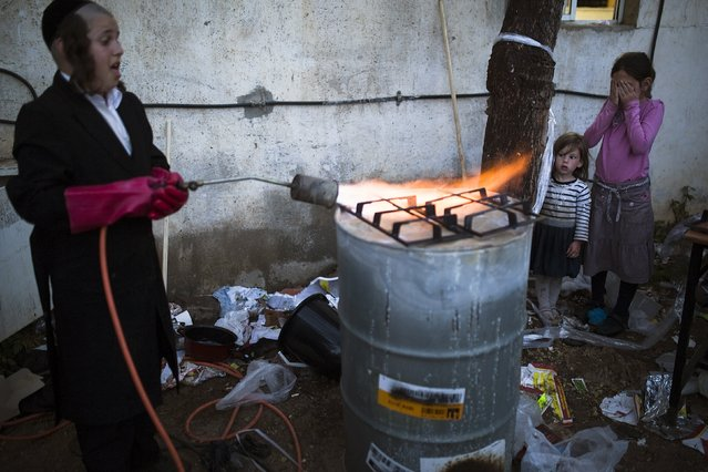 An ultra-Orthodox Jewish boy heats part of gas burner over a fire to remove remains of leaven in preparation for the upcoming Jewish holiday of Passover in the city of Ashdod April 2, 2015. Passover, which starts on Friday, commemorates the flight of Jews from ancient Egypt, as described in the Exodus chapter of the Bible. According to the account, the Jews did not have time to prepare leavened bread before fleeing to the promised land. (Photo by Amir Cohen/Reuters)
