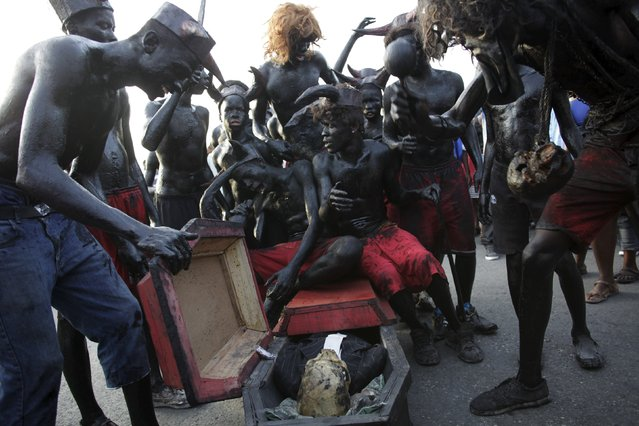 Revellers sit on a fake coffin containing a human skull as they take part in the Carnival 2016 parade in Port-au-Prince, Haiti, February 9, 2016. (Photo by Andres Martinez Casares/Reuters)