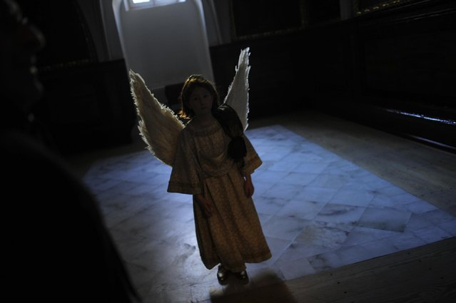 """Eight-year-old Alba Oroz,  wearing an angel costume takes part during the Easter Sunday ceremony """"Descent of the Angel"""", during Holy Week in the small town of Tudela, northern Spain, Sunday, April 5, 2015. (Photo by Alvaro Barrientos/AP Photo)"""