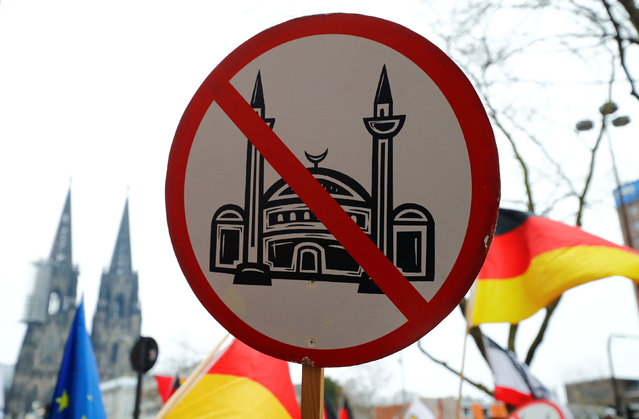An ultra-right-wing group gathers with a placard against mosques near the Cologne Cathedral (rear) during a demonstration against a gathering of ultra-right-wing groups to mark one year since hundreds of women were assaulted on New Year's Eve in Cologne, Germany January 7, 2017. (Photo by Wolfgang Rattay/Reuters)