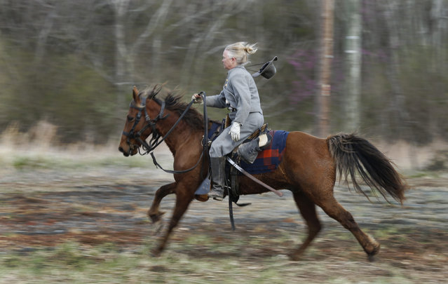 A Confederate re-enactor rides her horse back to friendly lines during a re-enactment of the Battle of Appomattox Station, Wednesday, April 8, 2015, as part of the 150th anniversary of the surrender of the Army of Northern Virginia to Union forces at Appomattox Court House, in Appomattox, Va. (Photo by Steve Helber/AP Photo)