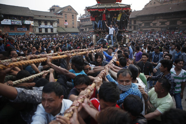 Nepalese devotees pull ropes tied to the chariot of Hindu god Bhairava during Bisket Jatra Festival in Bhaktapur, Nepal, Friday, April 10, 2015. During the festival, also regarded as Nepalese New Year, images of the Bhairava and his female counterpart Bhadrakali are enshrined in two large chariots and pulled to an open square after which rituals and festivities are performed. (Photo by Niranjan Shrestha/AP Photo)