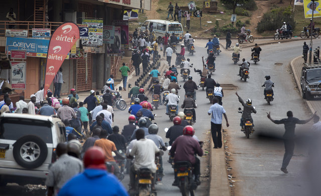 Opposition supporters who had attempted to gather, many of whom work as motorcycle taxi drivers, flee from police and soldiers as they chase them away, shortly after the election result was announced, in downtown Kampala, Uganda, Saturday, February 20, 2016. (Photo by Ben Curtis/AP Photo)
