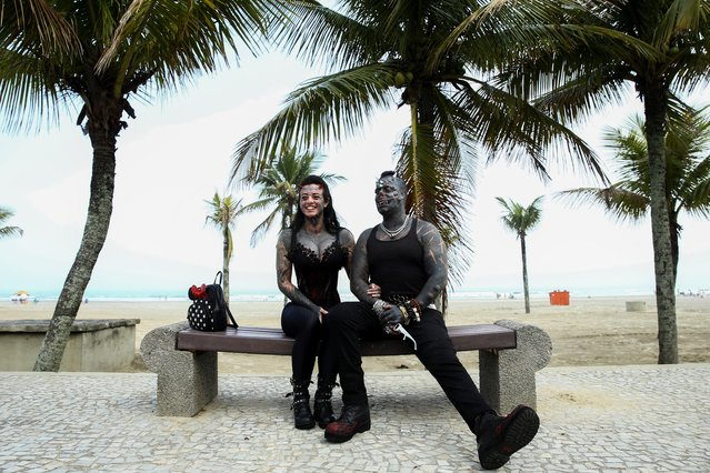 Brazilian tattoo artist Michel Praddo, also known as Diabao or Human Satan, and his wife Carol Praddo, known as Mulher Demonia or Demon Woman, sit on a bench at the beach shore in Praia Grande, Brazil on August 18, 2021. (Photo by Carla Carniel/Reuters)