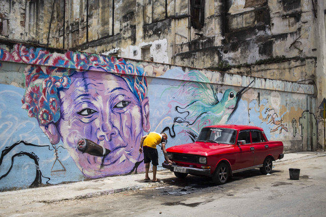 In this August 9, 2018 file photo, a man washes a car next to a mural of a woman smoking a cigar, in Havana, Cuba. The country is softening a heavily criticized new law known as Decree 349 that would have created a corps of powerful art inspectors able to shut down any exhibition or performance deemed to violate the country's socialist revolutionary values. Cuban authorities will announce complementary laws to the decree that will come into force on Friday, Dec. 7, 2018. (Photo by Desmond Boylan/AP Photo)