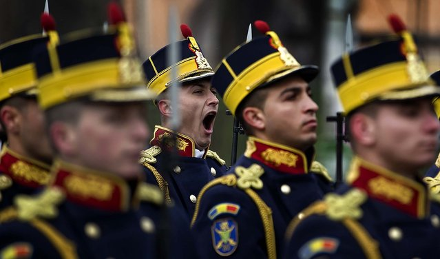 An honor guard soldier yawns during the commemoration of the 1989 anti-communist uprising, at the Heroes Cemetery in Bucharest, Romania, on December 21, 2013. The uprising, which left more than 1.000 dead, ended the rule of dictator Nicolae Ceausescu. (Photo by Vadim Ghirda/Associated Press)