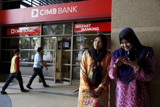 Women stand outside a CIMB bank branch in Putrajaya in this July 17, 2014 file photo.  CIMB is expected to report Q4 results this week. (Photo by Olivia Harris/Reuters)