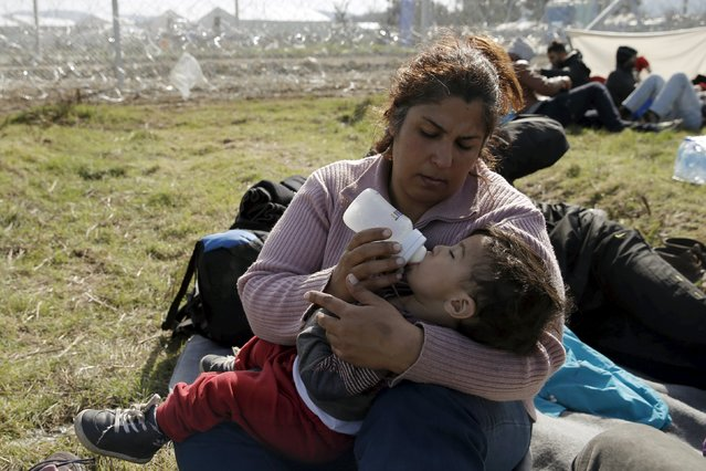 A migrant from Afghanistan feeds her child on a field next to a border fence at the Macedonian-Greek border in Gevgelija, Macedonia February 23, 2016. (Photo by Marko Djurica/Reuters)