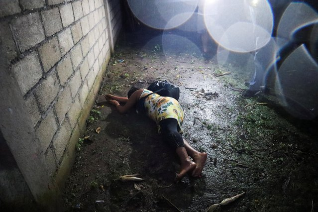 A migrant lies on the floor during an operation to halt the progress of a caravan of migrants and asylum seekers from Central America and the Caribbean as they moved toward Mexico City where they hoped to seek expedited asylum proceedings, in Mapastepec, in Chiapas state, Mexico, September 1, 2021. (Photo by Jose Torres/Reuters)