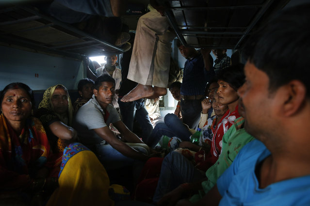 Indian commuters cramp on to an unreserved compartment of a train at the railway station in Allahabad, India, Thursday, February 25, 2016. (Photo by Rajesh Kumar Singh/AP Photo)