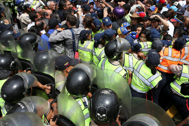 Opposition supporters clash with riot police during a rally against Venezuelan President Nicolas Maduro's government and to commemorate the 59th anniversary of the end of the dictatorship of Marcos Perez Jimenez in Caracas,Venezuela January 23, 2017. (Photo by Carlos Garcia Rawlins/Reuters)
