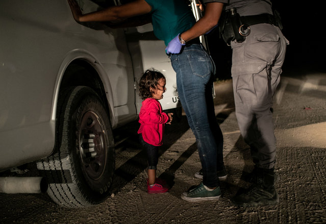 "Photo of the year nominee: crying girl on the border, by John Moore. Yanela, from Honduras, cries as her mother, Sandra Sanchez, is searched by a US border patrol agent, in McAllen, Texas, US. This image was also nominated in the ""spot news"" category. (Photo by John Moore/Getty Images/World Press Photo 2019)"