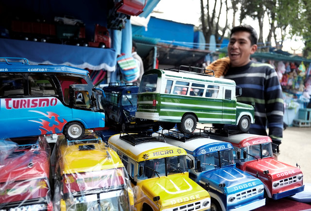 """A man looks at miniature vehicles during the """"Alasitas"""" fair, where people buy miniature versions of goods they hope to acquire in real life, in La Paz, Bolivia, January 24, 2017. (Photo by David Mercado/Reuters)"""