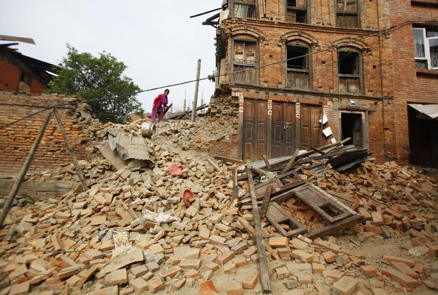 A Nepalese woman tries to find her belongings in the earthquake debris in Bhaktapur near Kathmandu, Nepal, Sunday, April 26, 2015. (Photo by Niranjan Shrestha/AP Photo)