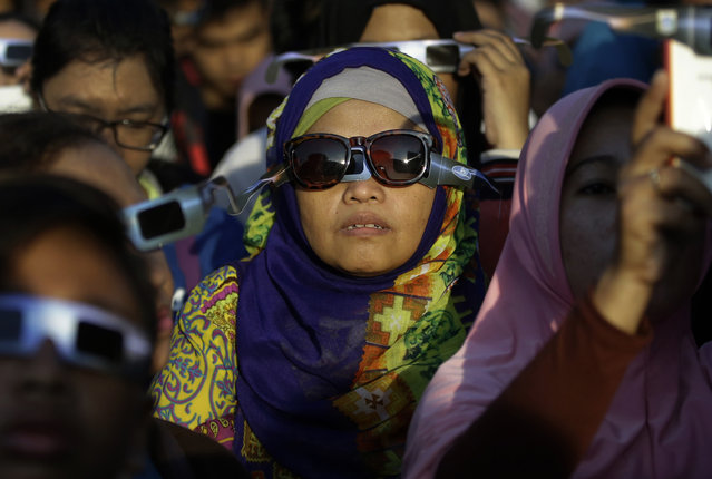 A Muslim woman looks up at the sun with protective glasses to watch a partial solar eclipse in Jakarta, Indonesia, Wednesday, March 9, 2016. (Photo by Dita Alangkara/AP Photo)