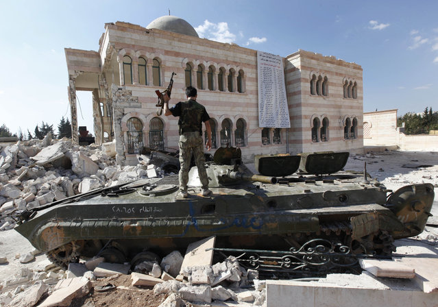 In this file photo taken on September 23, 2012, a Free Syrian Army soldier stands on a damaged Syrian military tank in front of a damaged mosque, which were destroyed during fighting with government forces, in the Syrian town of Azaz, on the outskirts of Aleppo. (Photo by Hussein Malla/AP Photo)