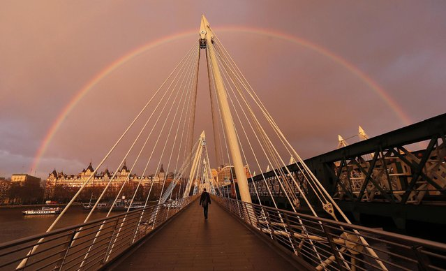 A rainbow appears as a pedestrian crosses the Hungerford Bridge in London January 31, 2014. (Photo by Suzanne Plunkett/Reuters)