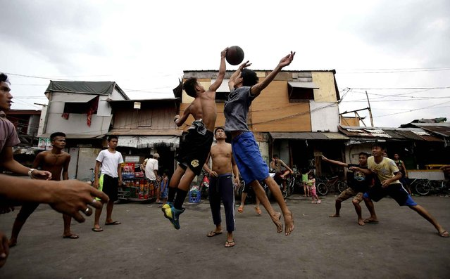 Filipinos jump for a basketball as they play at a slum in Manila, Philippines, Sunday, February 28, 2016. Basketball is a popular sport in the country. (Photo by Aaron Favila/AP Photo)