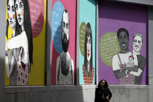 """Greek artist Fotini Tikkou poses below her artwork """"Out in the Street"""", part of a giant fresco to promote lesbian, gay, bisexual and transgender (LGBT) street art and to fight against homophobia and sexual discriminations, in central Brussels, Belgium May 1, 2015. (Photo by Francois Lenoir/Reuters)"""