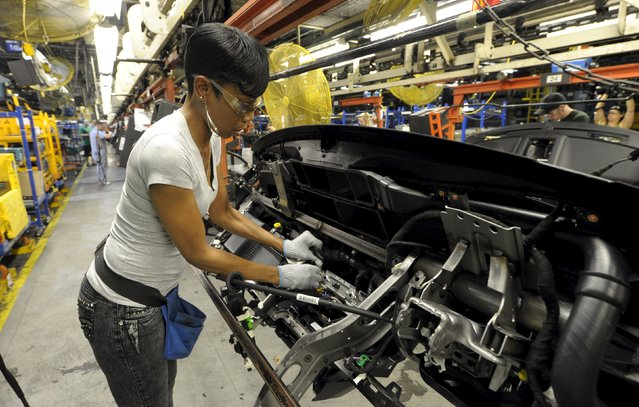 Auto worker Betty Smith assembles a dashboard at Ford's Kansas City Assembly Plant where new aluminum intensive Ford F-Series pickup is built in Claycomo, Missouri May 5, 2015. (Photo by Dave Kaup/Reuters)