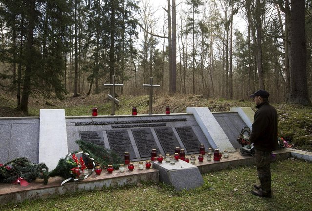 A man visits a monument, dedicated to the Polish and Belarussian people killed during World War Two, near the village of Pererov, southwest of Minsk, April 17, 2015. (Photo by Vasily Fedosenko/Reuters)