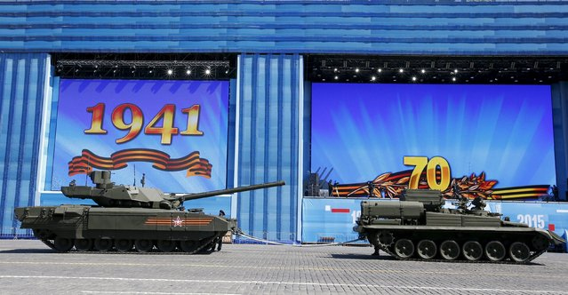 A T-14 Armata tank (L) comes to a stop during a rehearsal for the Victory Day parade in Red Square, with towing ropes attached to it, in central Moscow, Russia, May 7, 2015. (Photo by Grigory Dukor/Reuters)