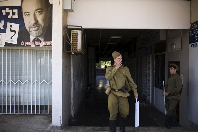 A youth wears the uniform of a World War Two veteran as he walks past a banner depicting  Avigdor Lieberman, head of the Yisrael Beiteinu party, during a parade marking the upcoming Victory Day, the anniversary of the Allied victory over Nazi Germany, in the southern city of Ashdod, Israel, May 8, 2015. Victory Day falls on May 9, with this year marking the 70th anniversary of the Allied victory. (Photo by Amir Cohen/Reuters)