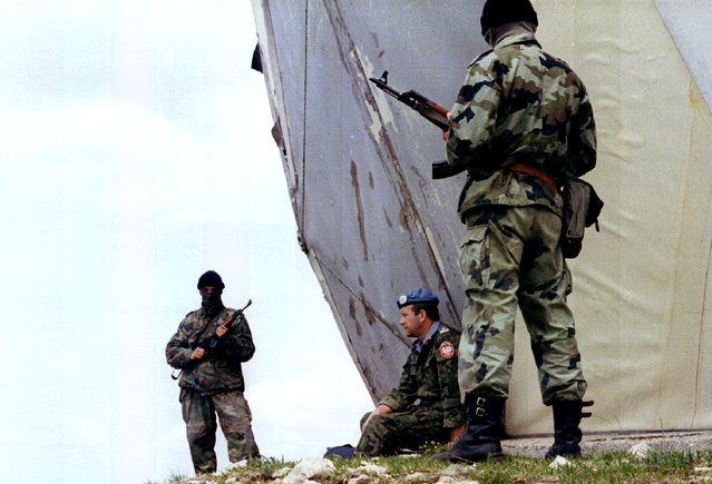 A Polish U.N. peacekeeper taken hostage by Bosnian Serbs in retaliation for NATO air strikes is chained to a radar station and guarded by two masked Bosnian Serb soldiers near Sarajevo, May 1995. (Photo by Reuters)