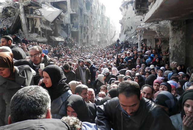A handout picture released by the United Nation Relief and Works Agency (UNRWA) on February 26, 2014 shows residents of Syria's besieged Yarmuk Palestinian refugee camp, south of Damascus, crowding a destroyed street during a food distribution led the UN agency, on January 31, 2014. (Photo by AFP Photo/UNRWA)