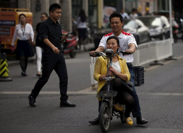 A couple rides a bicycle at a financial district in Beijing, China, May 5, 2015. (Photo by Kim Kyung-Hoon/Reuters)