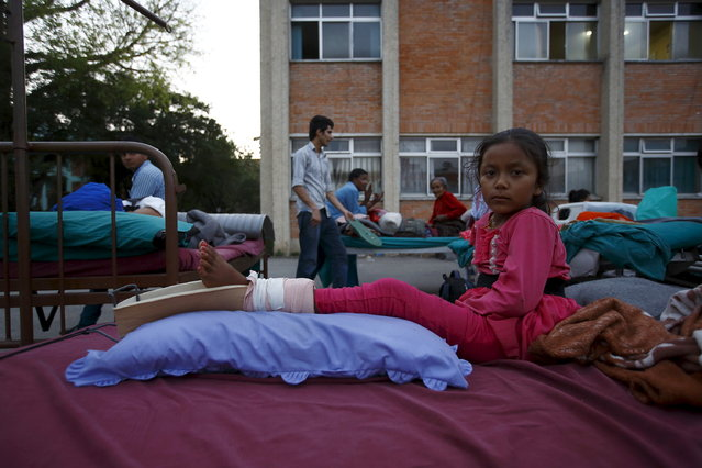 A girl lies on a bed after being moved out from the hospital to the open ground for treatment, in Kathmandu, May 12, 2015. (Photo by Navesh Chitrakar/Reuters)