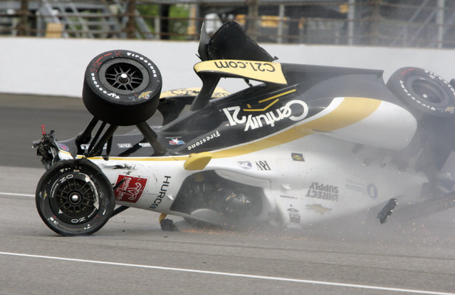 The car driven by Josef Newgarden slides down the track after hitting the wall in the first turn and going airborne during practice for the Indianapolis 500 auto race at Indianapolis Motor Speedway in Indianapolis, Thursday, May 14, 2015. (Photo by Joe Watts/AP Photo)