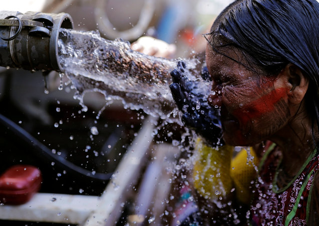 An indigenous woman from the Kayapo tribe washes her face near a water tanker at the Terra Livre camp, or Free Land camp, during a protest to defend indigenous land and cultural rights that the demonstrators say are threatened by the right-wing government of Brazil's President Jair Bolsonaro, in Brasilia, Brazil, April 24, 2019. (Photo by Nacho Doce/Reuters)