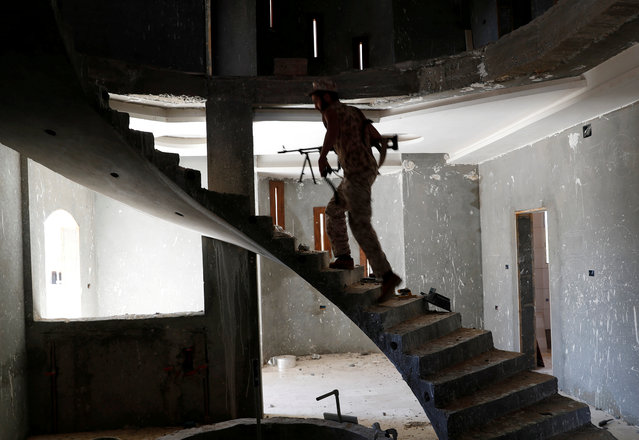 A fighter loyal to Libyan internationally recognised government walk inside a building at outskirts of Tripoli, Libya on May 16, 2019. (Photo by Goran Tomasevic/Reuters)