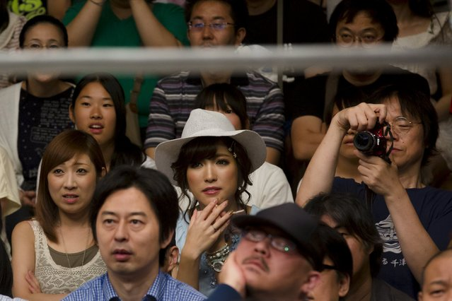 People watch women fight during a Stardom female professional wrestling show at Korakuen Hall in Tokyo, Japan, July 26, 2015. (Photo by Thomas Peter/Reuters)