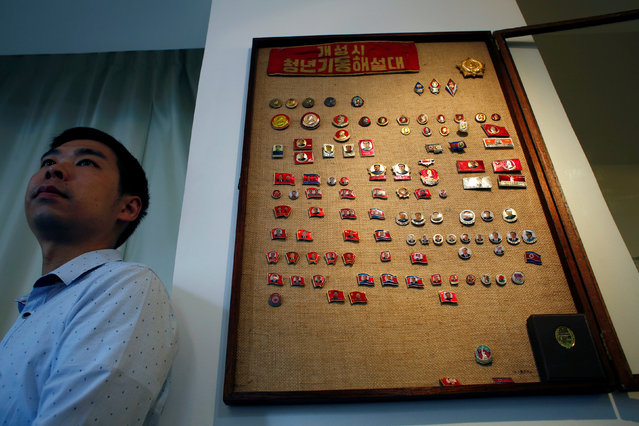 Thomas Hui poses with his glass case displaying more than 100 pins featuring former North Korean leaders Kim Il Sung and Kim Jong Il at his apartment in Hong Kong, China April 11, 2016. (Photo by Bobby Yip/Reuters)