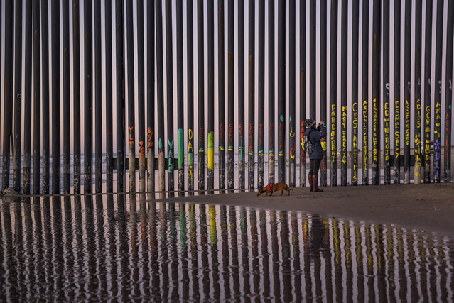 """In this January 3, 2019, file photo, a woman takes a photo by the border fence between San Diego, Calif., and Tijuana, as seen from Mexico. The top House Republican says a bipartisan border security compromise that Congress hopes to produce doesn't have to include the word """"wall"""". (Photo by Daniel Ochoa de Olza/AP Photo)"""