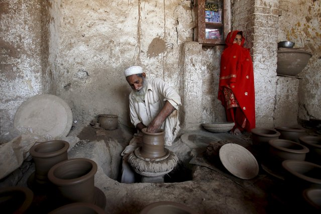 Haji Wazir, 60, puts the final touches on a clay pot for plants while his granddaughter Saima, 10, stands in the corner at a workshop in Peshawar April 13, 2015. (Photo by Fayaz Aziz/Reuters)