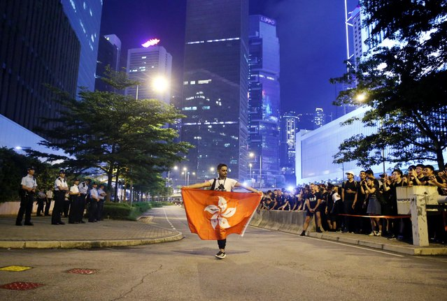 A protester holds a flag of Hong Kong as he attends a demonstration demanding Hong Kong's leaders to step down and withdraw the extradition bill, outside Office of the Chief Executive in Hong Kong, China, June 16, 2019. (Photo by Thomas Peter/Reuters)