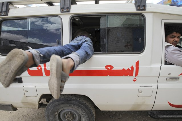 A boy enters through the window of a Yemen Red Crescent vehicle taking displaced people to a another safe shelter after they lived few days in an underground water tunnel, after they were forced to flee their homes due to ongoing air-strikes carried out by the Saudi-led coalition in Sanaa May 2, 2015. (Photo by Mohamed al-Sayaghi/Reuters)
