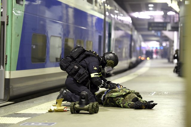 A member of the National Gendarmerie Intervention Group (GIGN) deactivates a bomb from a supposed terrorist during a training exercise in the event of a terrorist attack in collaboration with Recherche Assistance Intervention Dissuasion (RAID) and Research and Intervention Brigades (BRI) in presence of the French Interior minister Bernard Cazeneuve at la Gare Montparnasse, in central Paris on April 20, 2016. (Photo by Miguel Medina/Reuters)