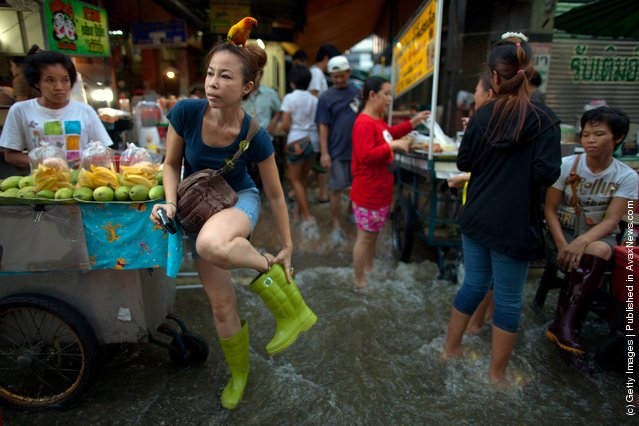 Patarawan fixes her boots as her parrot, Sim sits on her head as she goes shopping for dinner at a busy flooded market near the Chao Phraya river