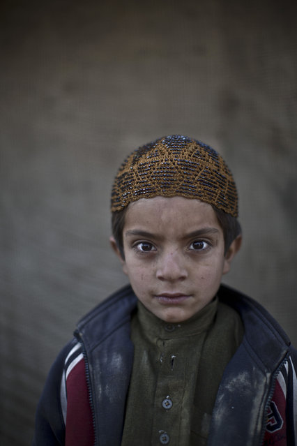 In this Monday, January 27, 2014 photo, Afghan refugee boy, Allam Ahmad, 6, poses for a picture, while playing with other children in a slum on the outskirts of Islamabad, Pakistan. (Photo by Muhammed Muheisen/AP Photo)
